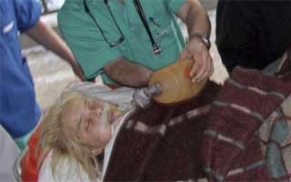 Ukrainian medical staff assist Oksana Makar, the victim of a vicious attack in the southern town of Mykolayiv, as she is brought for treatment to a hospital in Donetsk. She died of her injuries nearly three weeks later. | Photo: Reuters